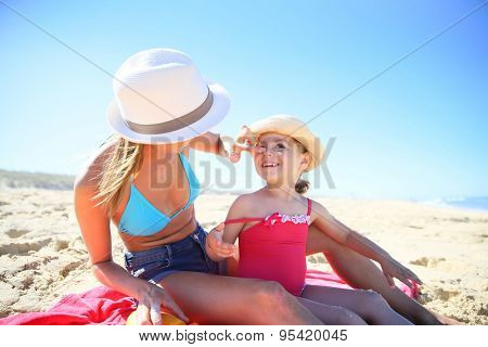 Woman applying sunscreen on daughter's body