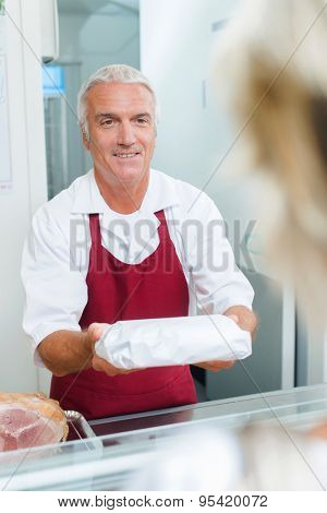 Butcher passing a package to a customer