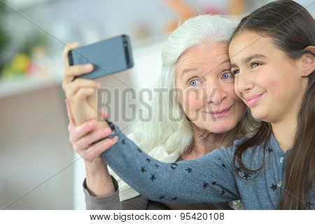 Little girl taking a selfie with her grandma