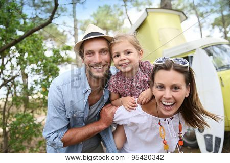 Couple with little girl enjoying vacation in camper van