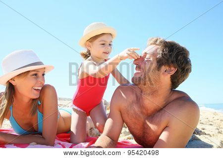 Family playing with seashells on the beach