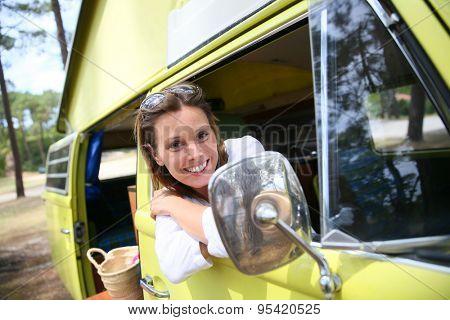 Portrait of cheerful woman sitting in vintage camper van