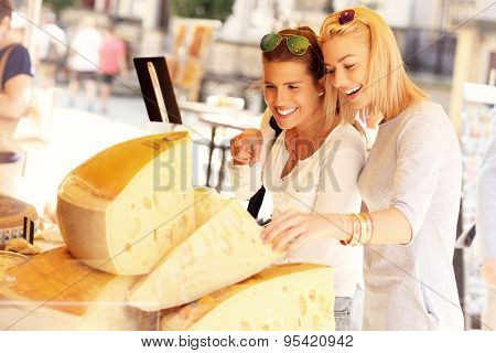 A picture of two tourists shopping for cheese on a food market