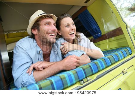 Cheerful young couple laying on a camper van