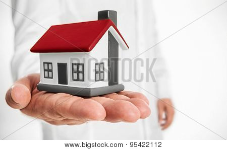 Business man holding model house