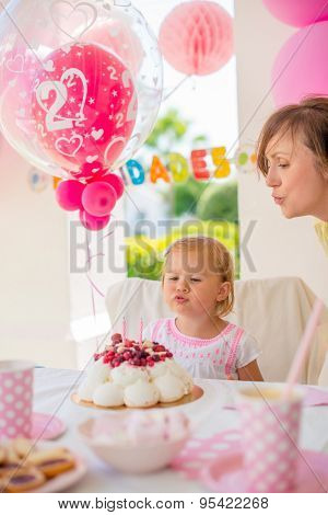 Garden party for the daughter 's birthday  with mum  Girl makes a wish and blows her candles