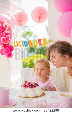 Sweet Cute Girl on Her Birthday Party  She Blowing Candles on Her Cake With a Little Help from Her Mum