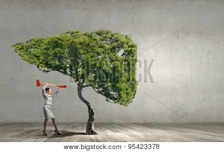 Businesswoman with axe representing problem of deforestation