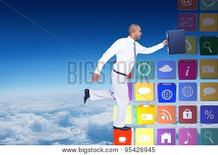 Businessman running with briefcase against blue sky over clouds at high altitude