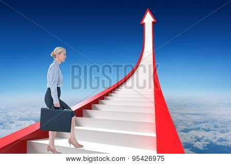 Businesswoman climbing with briefcase against blue sky over clouds at high altitude