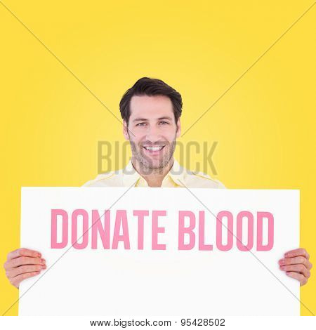 Attractive man smiling and holding poster against yellow vignette