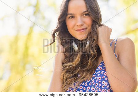 Pretty brunette with headphones on a sunny day