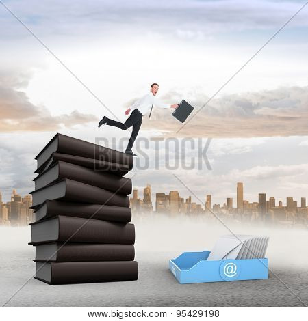 Happy businessman leaping with his briefcase against large city on the horizon