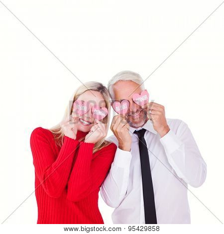 Silly couple holding hearts over their eyes against blood donor