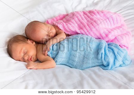Newborn twins sleeping in cuddle together
