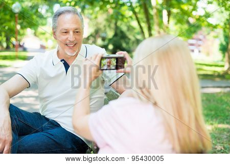 Wife using a compact camera to take a portrait of her husband in a park