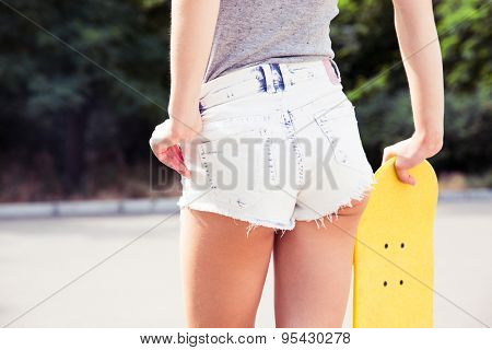 Back view portrait of a young female ass in shorts with skateboard outdoors