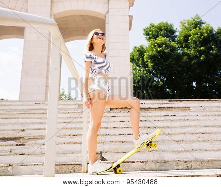 Smiling female skater in sunglasses standing outdoors and looking up