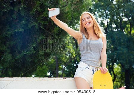 Happy young girl with skateboard making selfie photo on smartphone outdoors