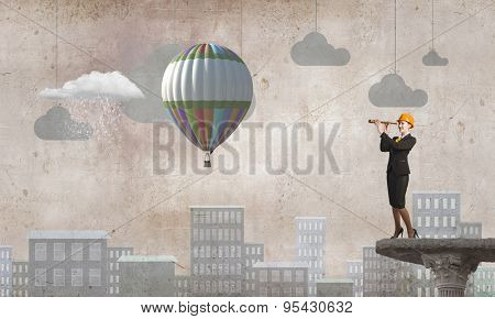 Young woman engineer on top looking in spyglass
