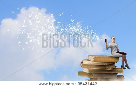 Young businesswoman holding mobile phone with flying out icons