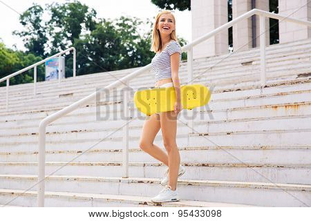 Full length portrait of a laughing female skater looking away outdoors