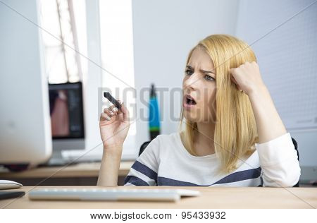 Shocked young woman working on computer in office