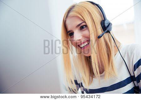 Happy young girl in headset using desktop computer in office