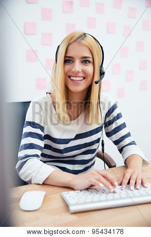 Young casual girl in headset working in office