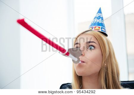 Young girl with party hat and blows whistle