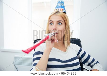 Casual woman with party hat and blows whistle