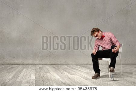 Guy sitting on chair and stepping on small business person