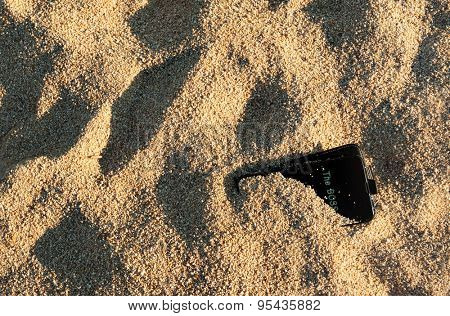 A black smart phone left buried in the send on a beach with the boss calling.