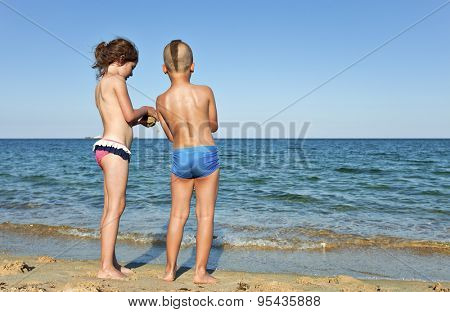 A boy and a girl, about 7 years old, back to dthe camera, sharing time on an emty beach in the summer.