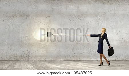 Young businesswoman with suitcase pulling light bulb on lead