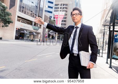 Businessman trying to catch a taxi in business cuty district