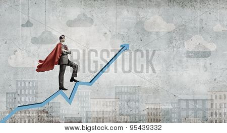 Young man in super hero costume standing on increasing graph