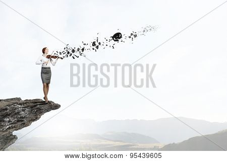 Young pretty businesswoman on rock edge playing violin