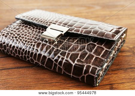Manicure set in closed leather case on wooden background