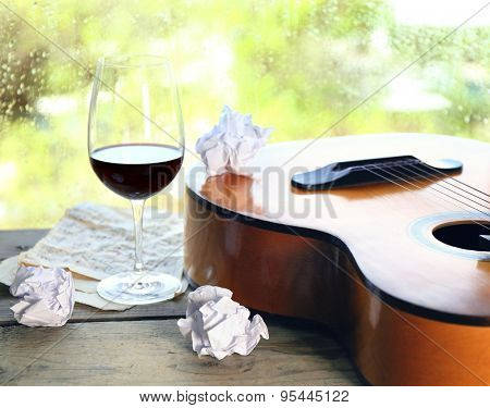 Acoustic guitar and glass of wine next the window with rain drops