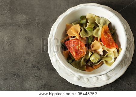 Roasted asparagus and tasty colorful pasta with vegetables in bowl on colorful background