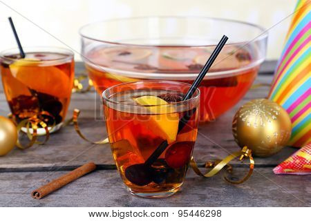 Sangria in bowl and glasses on light background