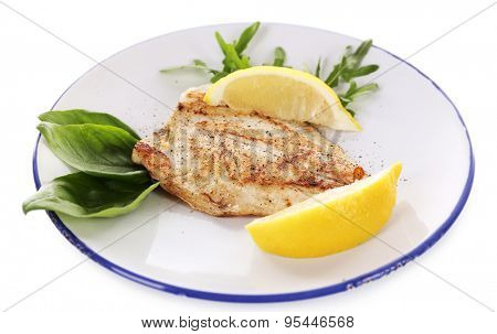 Dish of fish fillet with greens and lemon on plate isolated on white