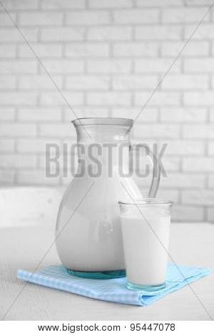 Pitcher and glass of milk on wooden table, on bricks wall background