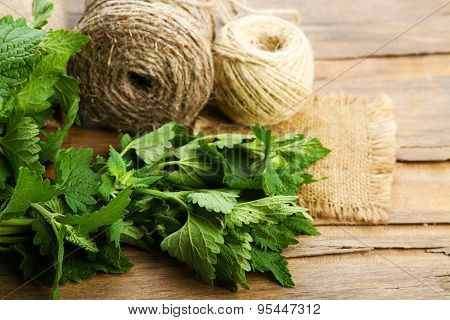 Leaves of lemon balm with rope on wooden table, closeup