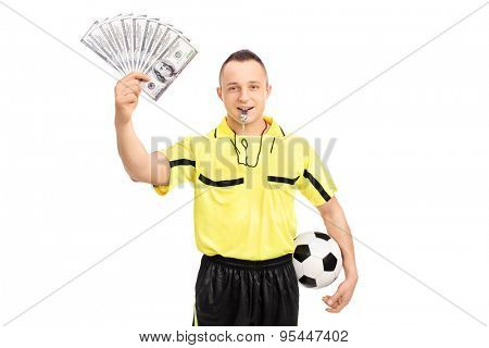 Young male football referee holding a stack of money and looking at the camera isolated on white background