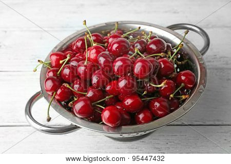 Sweet cherries in colander on table close up