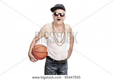 Cheerful senior in hip hop clothes holding a basketball and looking at the camera isolated on white background