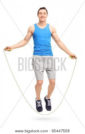 Full length portrait of a young man exercising with a skipping rope and looking at the camera isolated on white background