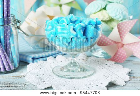 Sweet candies in glassware on wooden table, closeup
